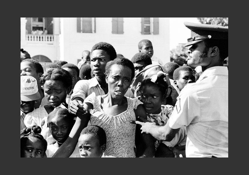Policier contenant la foule lors de la remise des cadeaux de Noël par la présidente Michelle Duvalier devant les grilles du palais National, Port au Prince Haïti 1981.