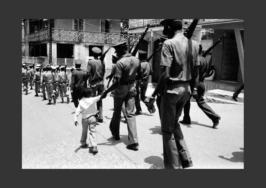 Enfant au milieu d'une parade de Tontons Macoutes et de militaires, Jacmel Haïti 1982.