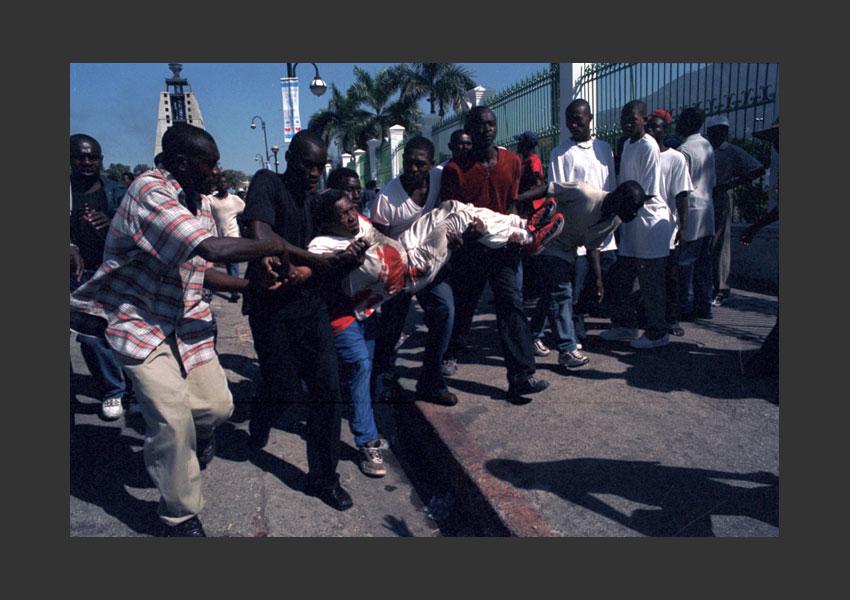 """Fin tragique de la manif fêtant le départ d'Aristide : place du Champs de Mars, du haut d'immeubles des """"Chimères"""" snipers ont tirés sur la foule : bilan 7 morts dont le journaliste espagnol Ricardo Ortega et plus de 40 blessés. Dimanche 7 Mars 2004 Haïti."""